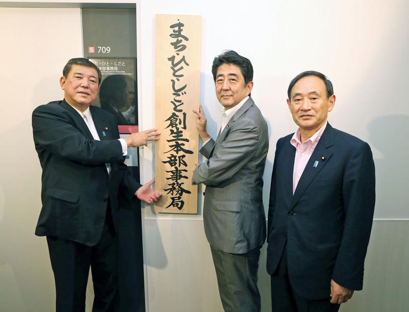 2014年9月、「まち・ひと・しごと創生本部事務局」の看板を掛ける石破地方創生相(左)と安倍首相。右は菅官房長官=東京・永田町